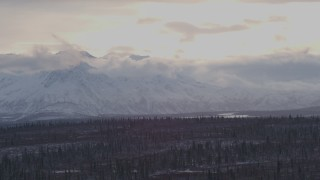 AK0001_1051 - 4K stock footage aerial video snow and cloud capped Chugach Mountains near forest, Alaskan Wilderness