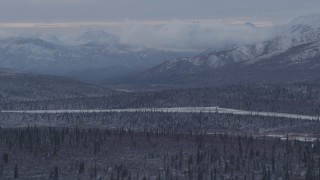AK0001_1054 - 4K stock footage aerial video snow capped Talkeetna Mountains and wooded foothills, Alaskan Wilderness