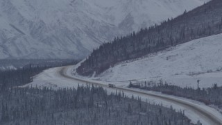 AK0001_1055 - 4K stock footage aerial video Glenn Highway winding around snowy Talkeetna Mountain, Alaskan Wilderness