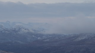 AK0001_1058 - 4K stock footage aerial video low clouds eclipsing snowy Talkeetna Mountains, Alaska
