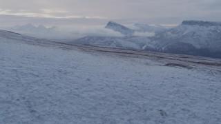 AK0001_1061 - 4K stock footage aerial video flying over a snowy slope toward Talkeetna Mountains, Alaska