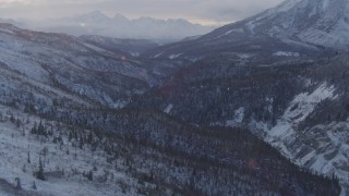 AK0001_1064 - 4K stock footage aerial video snow covered wooded hills, river through valley, Talkeetna Mountains, Alaska