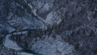 AK0001_1065 - 4K stock footage aerial video a river at bottom of wooded, snowy canyon, Talkeetna Mountains, Alaska