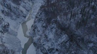 AK0001_1067 - 4K stock footage aerial video river at bottom of snowy canyon, forest topped cliffs, Talkeetna Mountains, Alaska