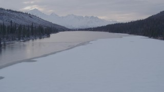 AK0001_1072 - 4K stock footage aerial video flying over snow covered trees and lake, Matanuska River Valley, Alaska