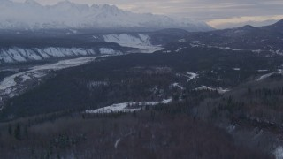 AK0001_1074 - 4K stock footage aerial video a snowy, wooded slope, revealing Sutton, Matanuska River Valley, Alaska