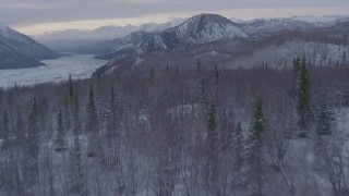AK0001_1090 - 4K stock footage aerial video flying over snow covered, wooded hills toward Matanuska River Valley, Alaska