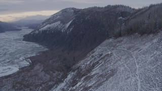AK0001_1095 - 4K stock footage aerial video ascending a snow covered cliff in the Matanuska River Valley, Alaska