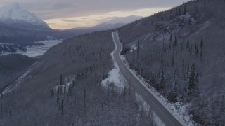 AK0001_1100 - 4K stock footage aerial video follow Glenn Highway, snow covered, wooded hills, Sutton, Alaska, twilight