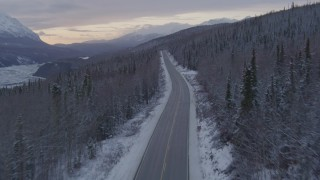 AK0001_1101 - 4K stock footage aerial video following Glenn Highway and snow covered forest near Sutton at twilight, Alaska