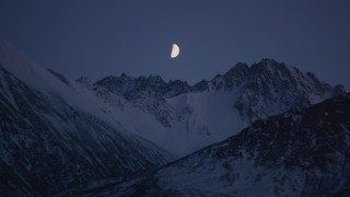 AK0001_1105 - 4K stock footage aerial video the moon over the snow covered Chugach Mountains at night, Alaska