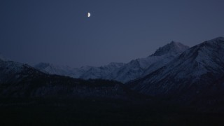 AK0001_1108 - 4K stock footage aerial video the moon over the snow covered Chugach Mountains at night, Alaska