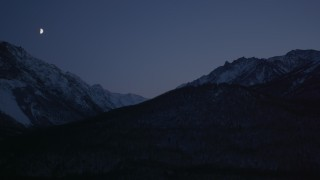 AK0001_1111 - 4K stock footage aerial video the moon over the snow covered Chugach Mountains at night, Alaska