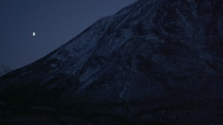 AK0001_1113 - 4K stock footage aerial video the moon over the snow covered Chugach Mountains at night, Alaska