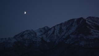 AK0001_1117 - 4K stock footage aerial video the moon over the snow covered Chugach Mountains at night, Alaska