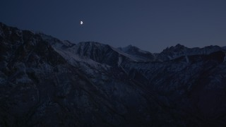 AK0001_1120 - 4K stock footage aerial video the moon over the snow covered Chugach Mountains at night, Alaska