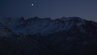 AK0001_1122 - 4K stock footage aerial video the moon over the snow covered Chugach Mountains at night, Alaska