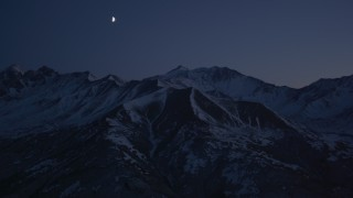 AK0001_1123 - 4K stock footage aerial video the moon over the snow covered Chugach Mountains at night, Alaska