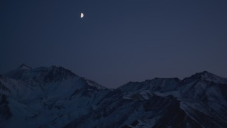 AK0001_1126 - 4K stock footage aerial video the moon over the snow covered Chugach Mountains at night, Alaska