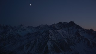 AK0001_1133 - 4K stock footage aerial video the moon over the snow covered Chugach Mountains at night, Alaska