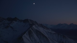 AK0001_1138 - 4K stock footage aerial video the moon above the snow covered Chugach Mountains at night, Alaska