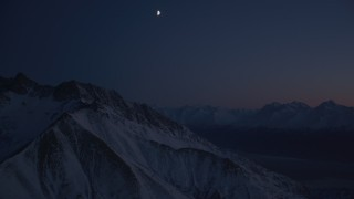AK0001_1139 - 4K stock footage aerial video the moon over snowy Chugach Mountains, tilt down to valley, Alaska, night