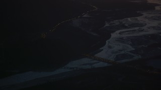 AK0001_1141 - 4K stock footage aerial video heavy traffic crossing Glenn Highway bridge at night, in snow, Alaska