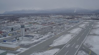 AK0001_1147 - 4K stock footage aerial video lift off from snowy Merrill Field, head across East 5th Ave, Anchorage, Alaska