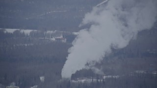AK0001_1150 - 4K stock footage aerial video a power plant, tilting up in plumes of steam, Anchorage, Alaska in snow