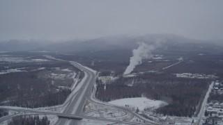 AK0001_1151 - 4K stock footage aerial video following Glenn Highway toward power plant in snow, Anchorage, Alaska