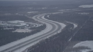 AK0001_1156 - 4K stock footage aerial video Glenn Highway winding past snowy Bryant Army Heliport, Anchorage, Alaska