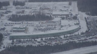AK0001_1157 - 4K stock footage aerial video snow covered buildings near Bryant Army Heliport, Anchorage, Alaska