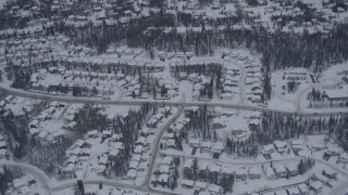 AK0001_1161 - 4K stock footage aerial video flying over snow covered neighborhoods and trees in Eagle River, Alaska