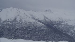 AK0001_1174 - 4K stock footage aerial video flying over snowy summit revealing wooded valley, Chugach Mountains, Alaska