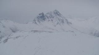 AK0001_1178 - 4K stock footage aerial video flying toward rocky, snow covered Chugach Mountain peak, Alaska