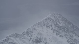AK0001_1209 - 4K stock footage aerial video wind blowing snow off mountain peak, Chugach Mountains, Alaska
