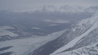 AK0001_1210 - 4K stock footage aerial video Butte and Knik River Valley at base of snow covered Chugach Mountains, Alaska