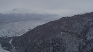 AK0001_1214 - 4K stock footage aerial video fly away from snowy, wooded slopes, Knik River Valley, Chugach Mountains, Alaska