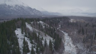 AK0001_1224 - 4K stock footage aerial video following a river next to snow covered, wooded hills, Knik River Valley, Alaska