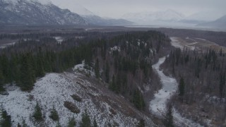 AK0001_1225 - 4K stock footage aerial video following a river next to wooded hills, Knik River Valley, Alaska