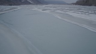 AK0001_1275 - 4K stock footage aerial video following an icy river over frozen banks, Butte, Alaska