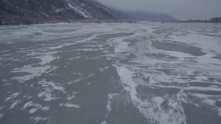 AK0001_1276 - 4K stock footage aerial video flying over frozen ground and iced over rivers, Butte, Alaska