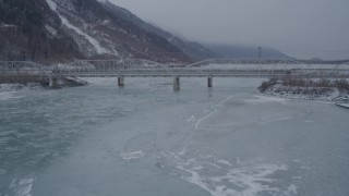 AK0001_1277 - 4K stock footage aerial video flying over frozen ground toward Old Glenn Highway bridge, Butte, Alaska in snow