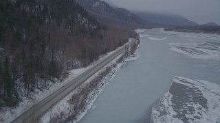 AK0001_1278 - 4K stock footage aerial video following Old Glenn Highway next to an icy river and snow, Butte, Alaska