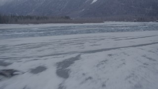 AK0001_1296 - 4K stock footage aerial video flying over a snowy riverbank and icy river, Knik River Valley, Alaska