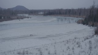 AK0001_1298 - 4K stock footage aerial video ascending over trees, snowy riverbank, icy river, Knik River Valley, Alaska