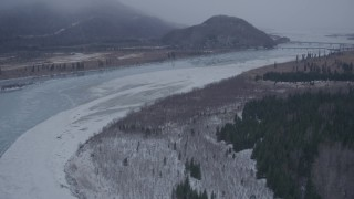 AK0001_1300 - 4K stock footage aerial video flying over icy river toward Glenn Highway bridge, Knik River Valley, Alaska in snow