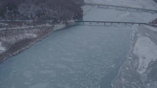 AK0001_1301 - 4K stock footage aerial video fly over snowy shore, Glenn Highway, Highway 1 bridge, Knik River Valley, Alaska