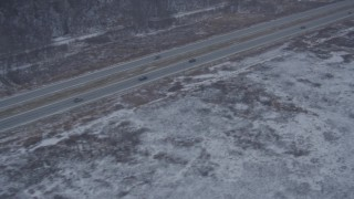 AK0001_1304 - 4K aerial stock footage video following Glenn Highway through snow covered ground, Anchorage, Alaska