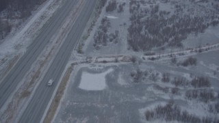 AK0001_1306 - 4K stock footage aerial video following Glenn Highway through falling snow, Anchorage, Alaska